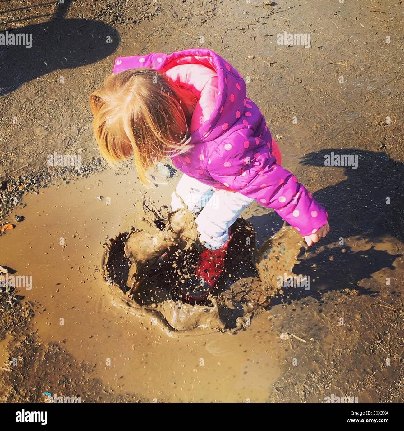 Girl toddler jumping up and down in muddy puddles - Stock Image