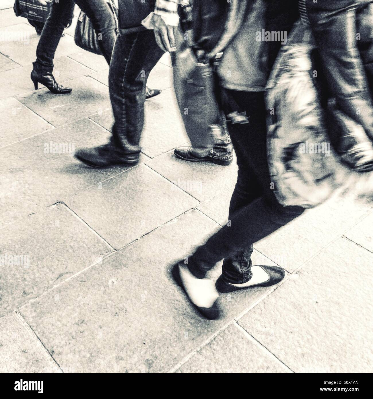 Motion blur of people walking by - Stock Image