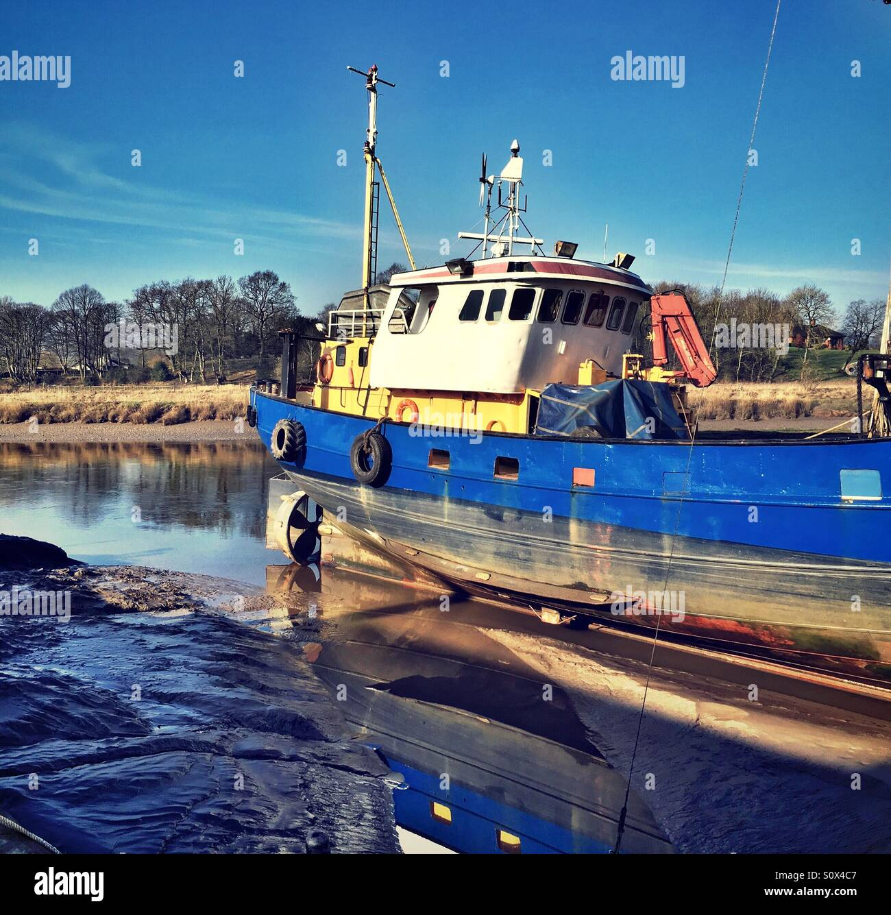 Boat harboured tide out - Stock Image