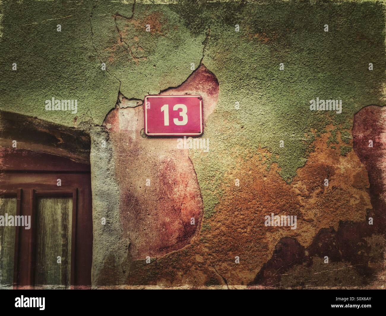 House number 13 on a peeling colorful facade - Stock Image