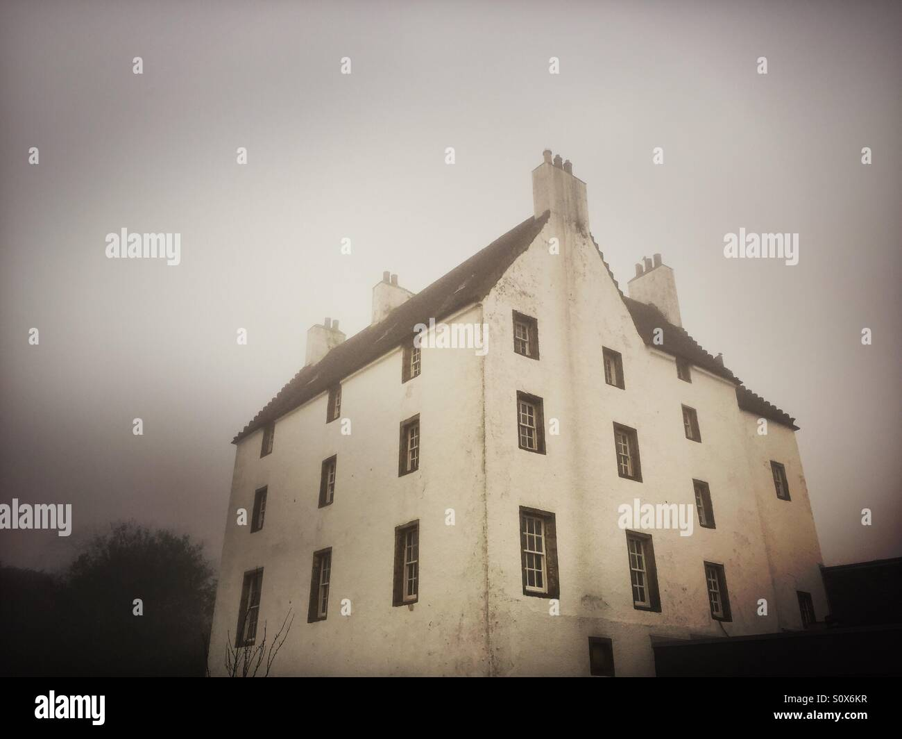 A large house is seen in the mist in Upphall, near Edinburg in Scotland. - Stock Image