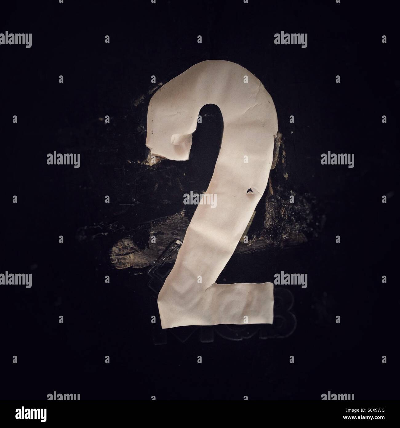 Scrappy tatty stuck-on number 2. - Stock Image
