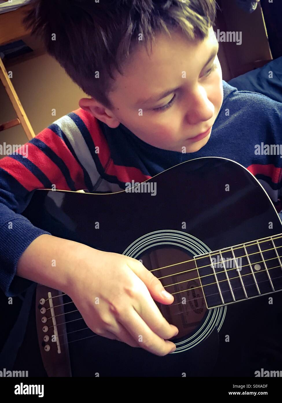 11 year old boy playing his guitar in the morning - Stock Image