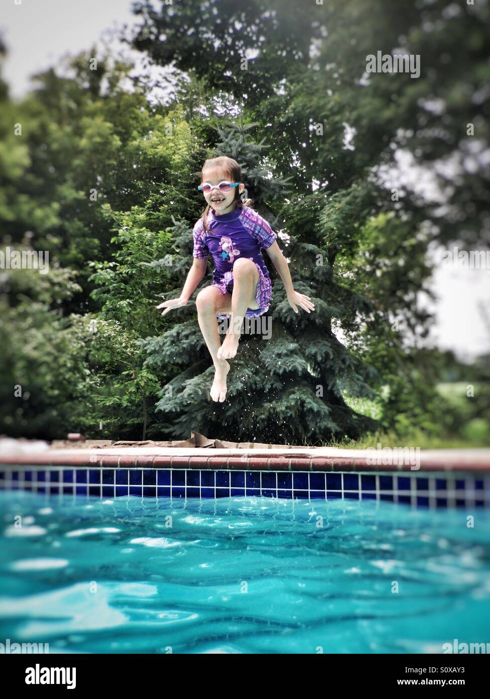 Girl wearing purple suit and swim goggles jumping into a swimming pool - Stock Image