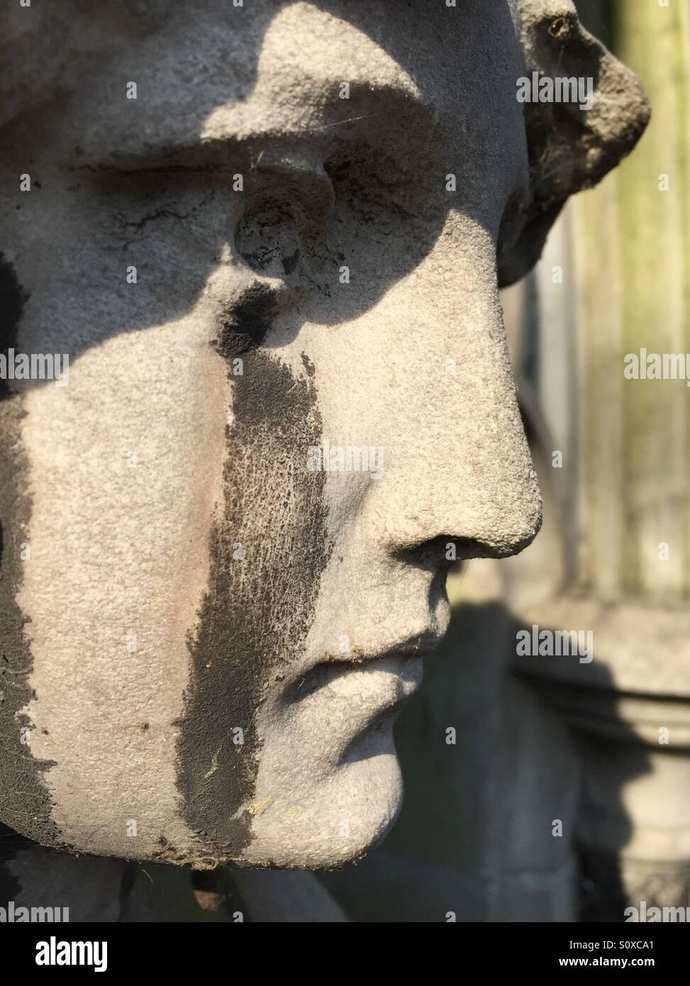 Tombstone sculpture with acid rain tears. Brompton cemetery, Kensington, London, England - Stock Image