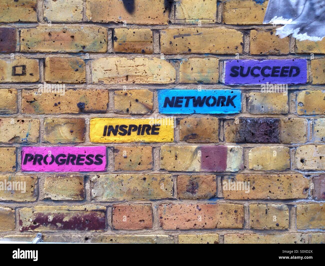 Street art in the area of Brick Lane, Shoreditch, East London, UK: coloured bricks with inspirational concepts progress, - Stock Image