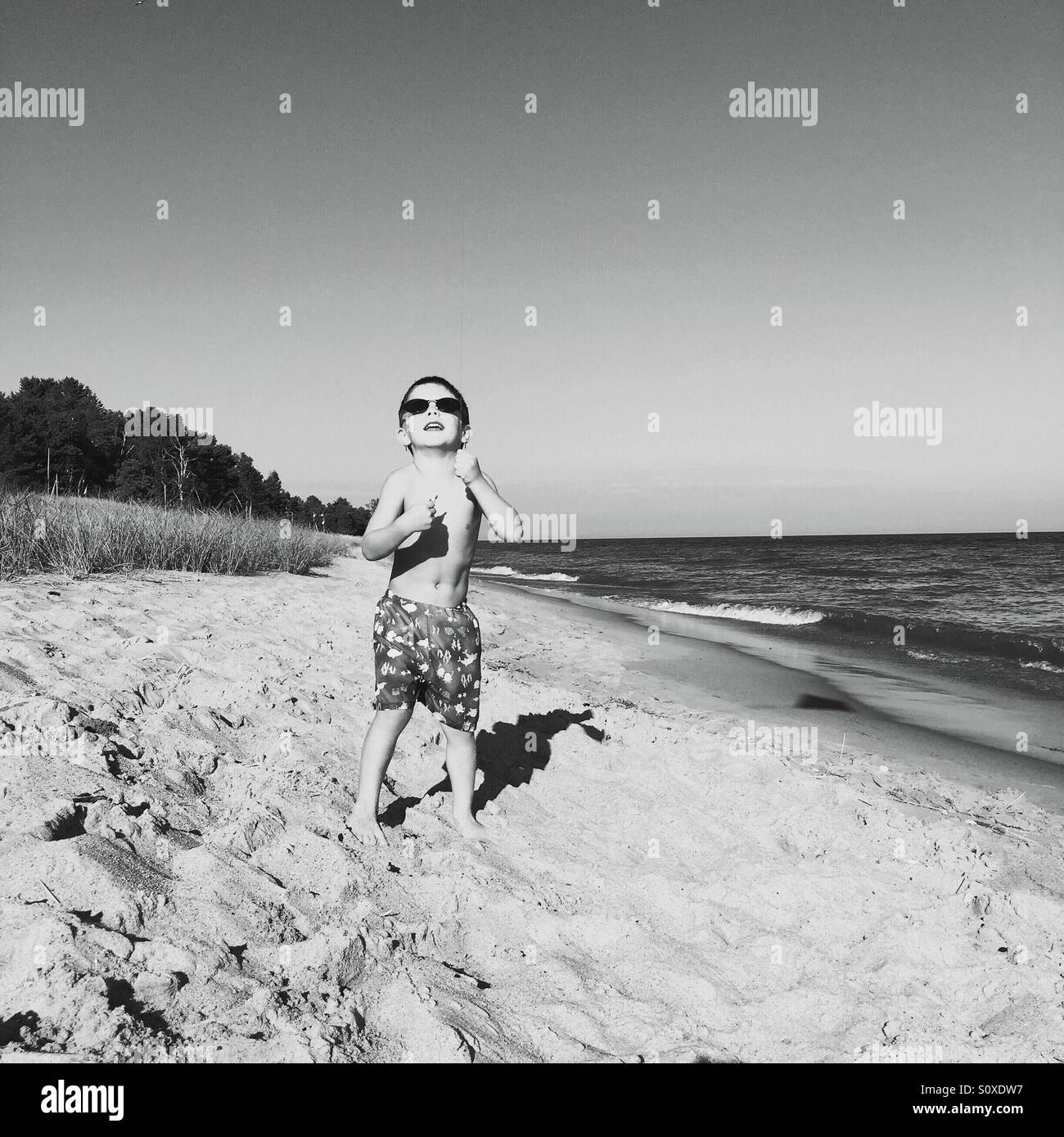 Back and white image of a young boy wearing sunglasses flying a kite on the beach. - Stock Image