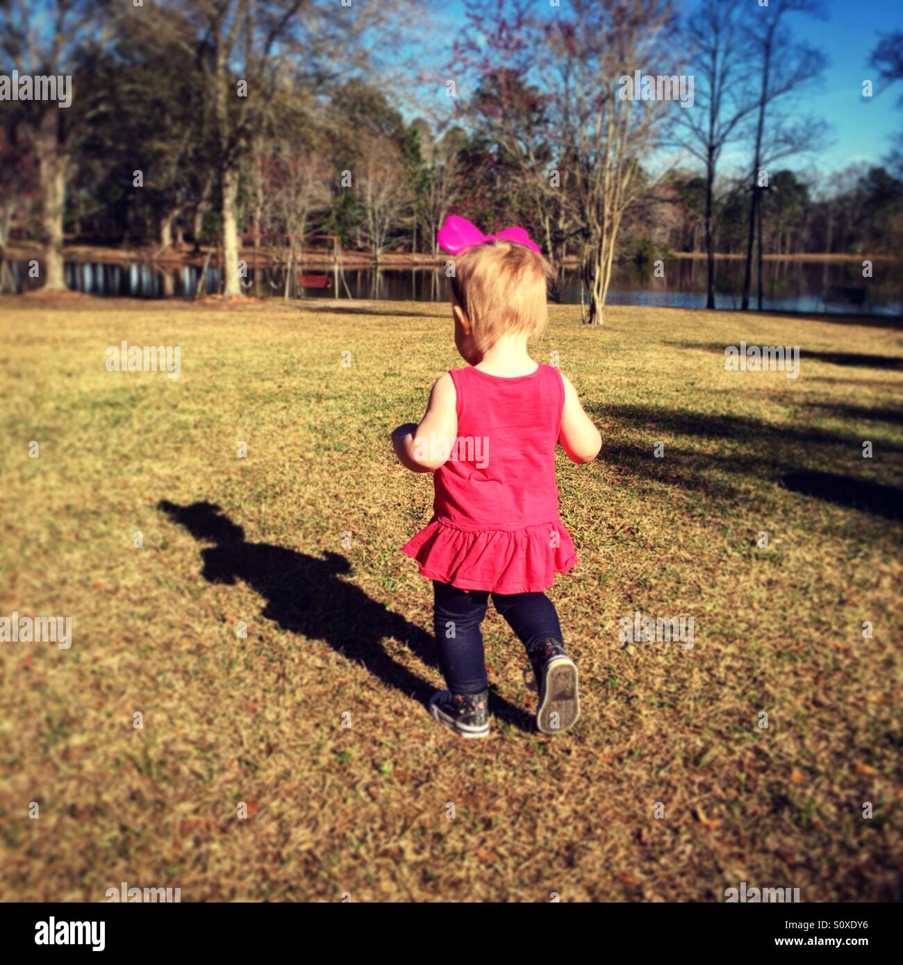 Baby girl outside chasing shadow - Stock Image