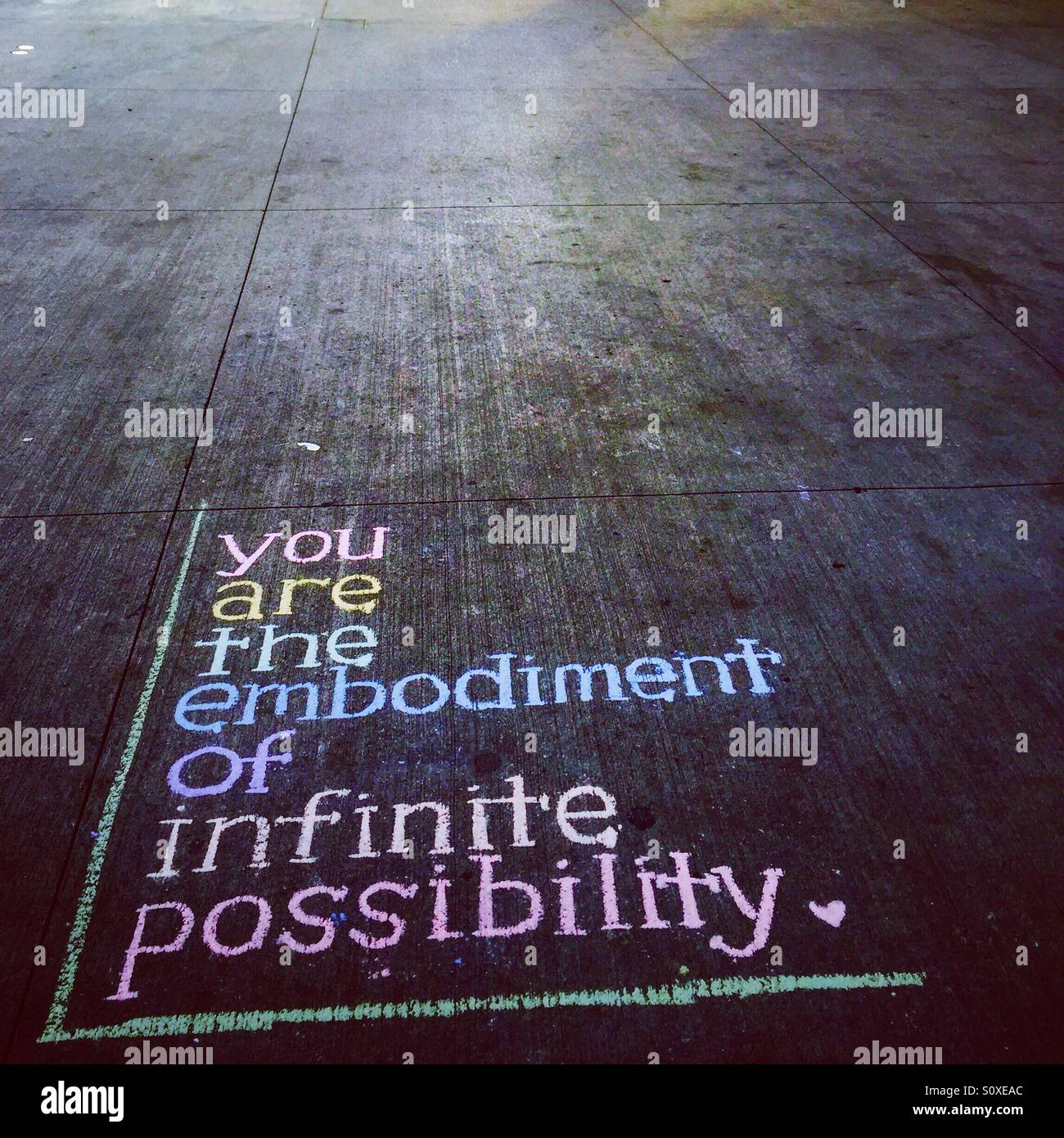 You are the embodiment of infinite possibility inspirational quote on pavement in NYC - Stock Image
