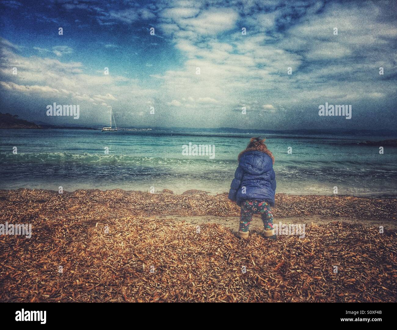 Baby At the beach in winter - Stock Image