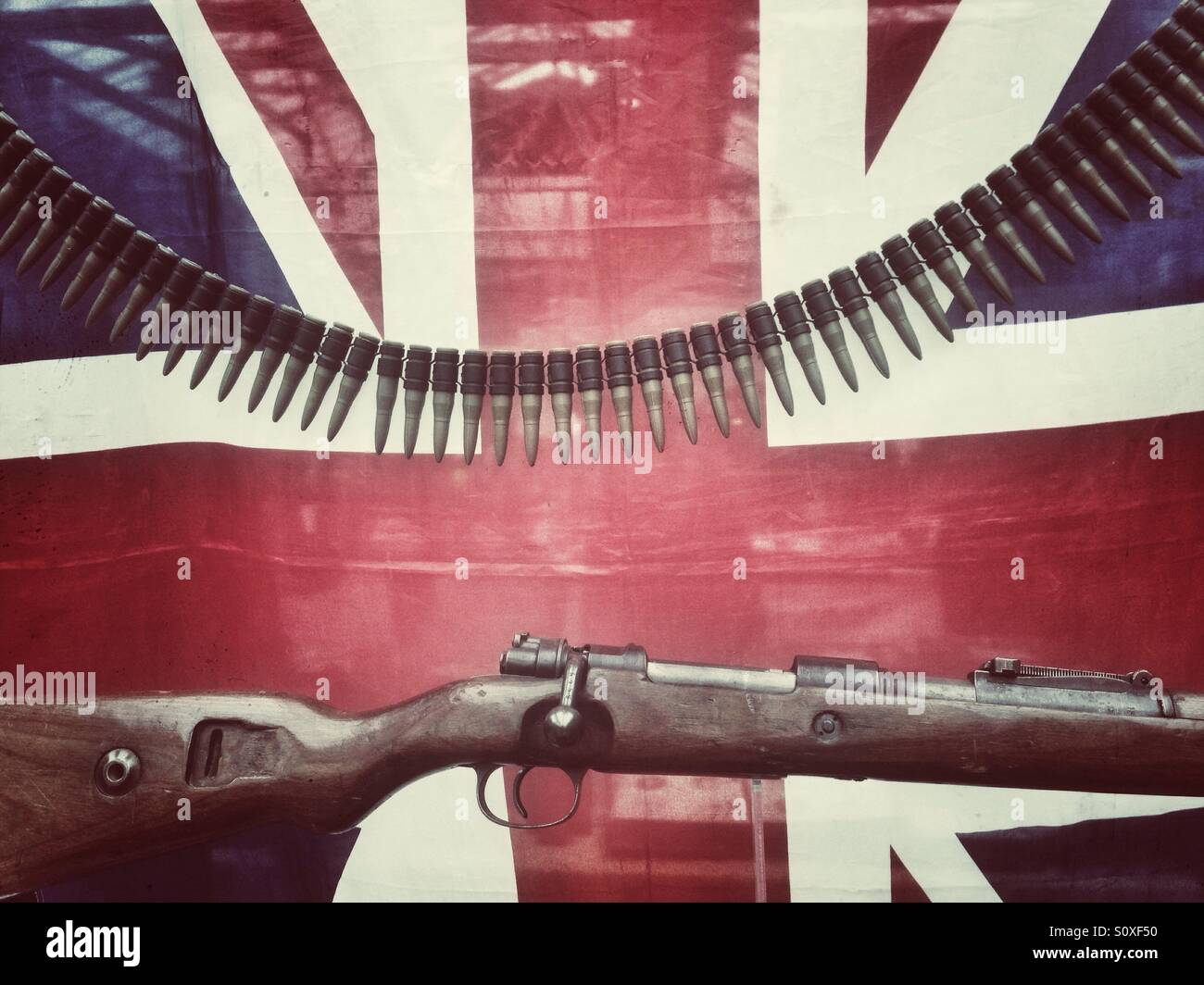 A military rifle and ammunition in front of a union jack - Stock Image