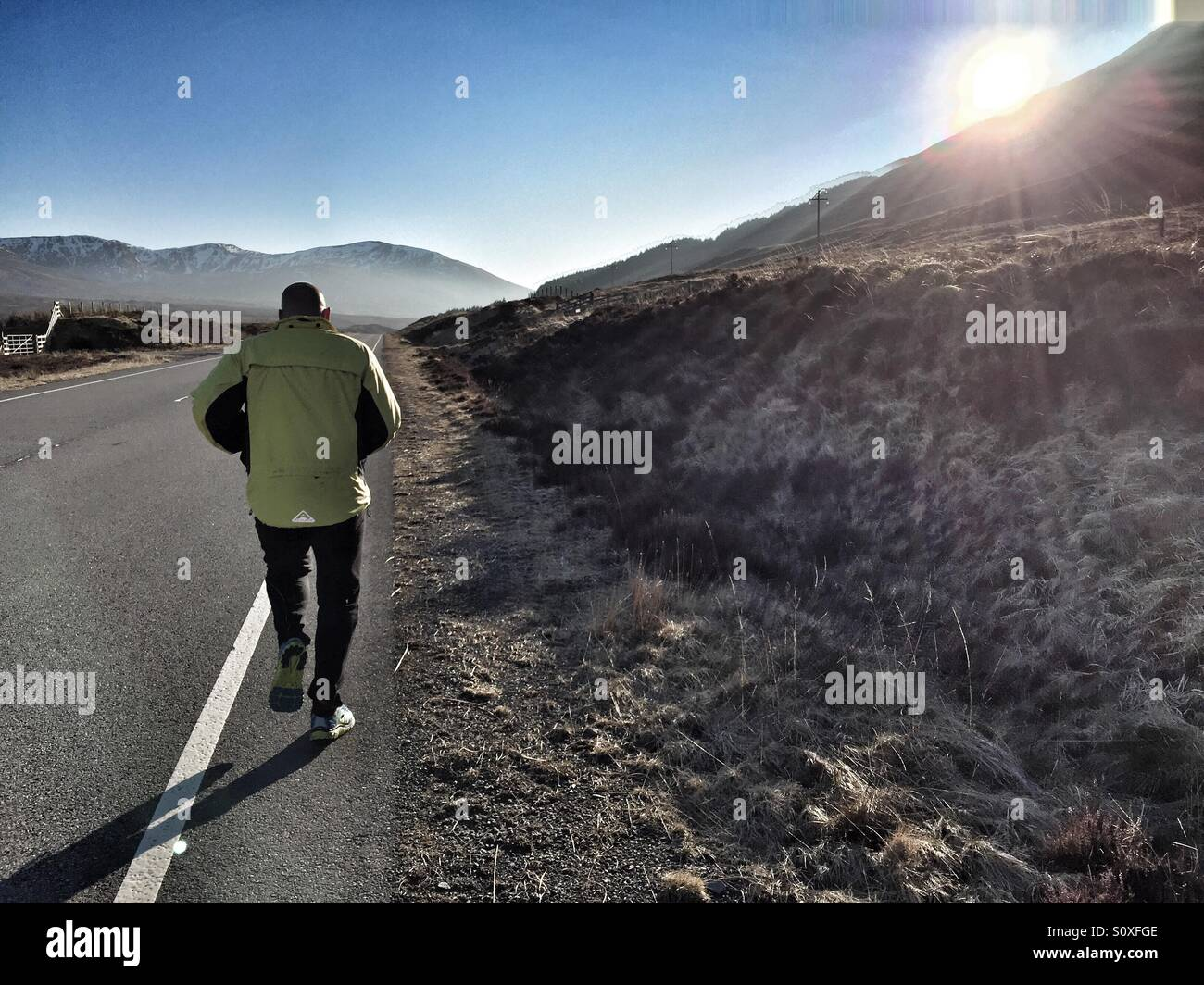 The freedom of the open road. 40 year old man running on a mountain road - Stock Image