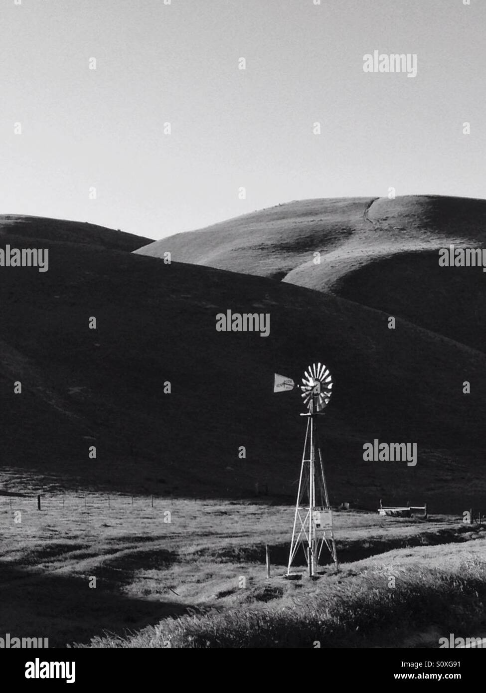 Windmill in hilly ranch country, in black and white - Stock Image