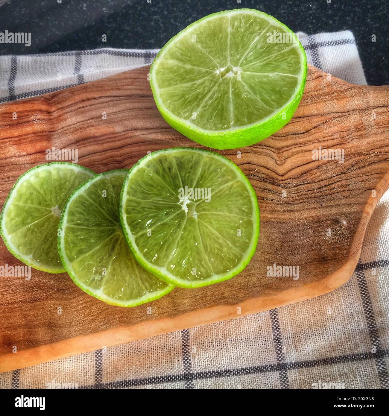 Sliced limes resting on a olive wood platter - Stock Image