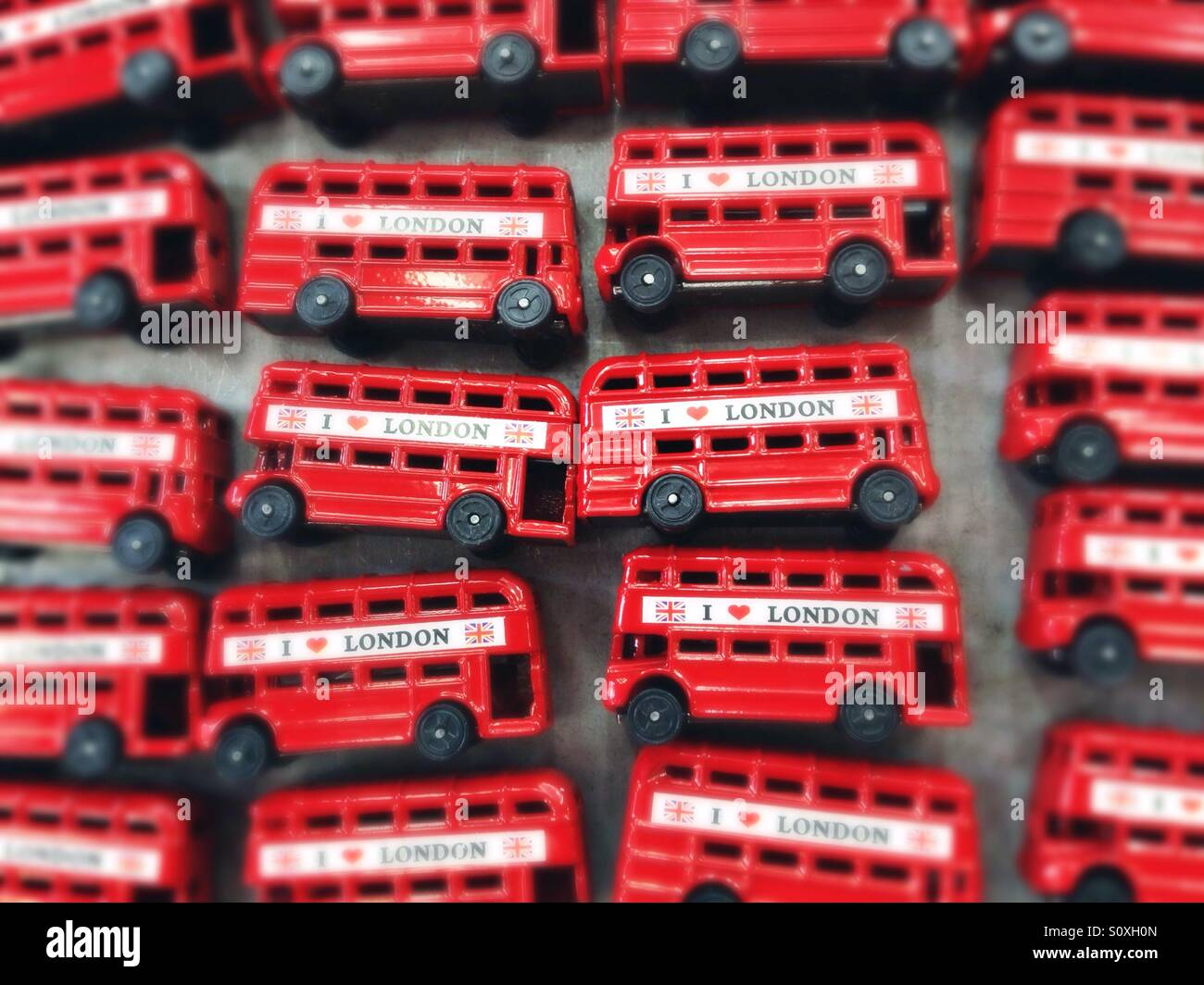 Red busses sold as souvenirs in Camden Town, London, UK - Stock Image