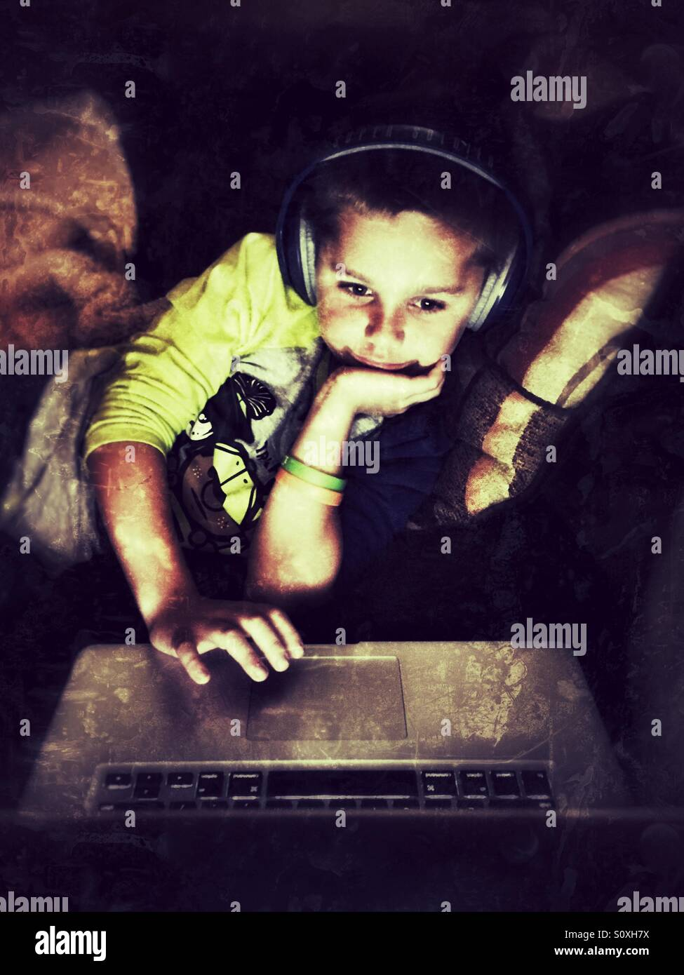 Young boy with headphones uses a laptop - Stock Image