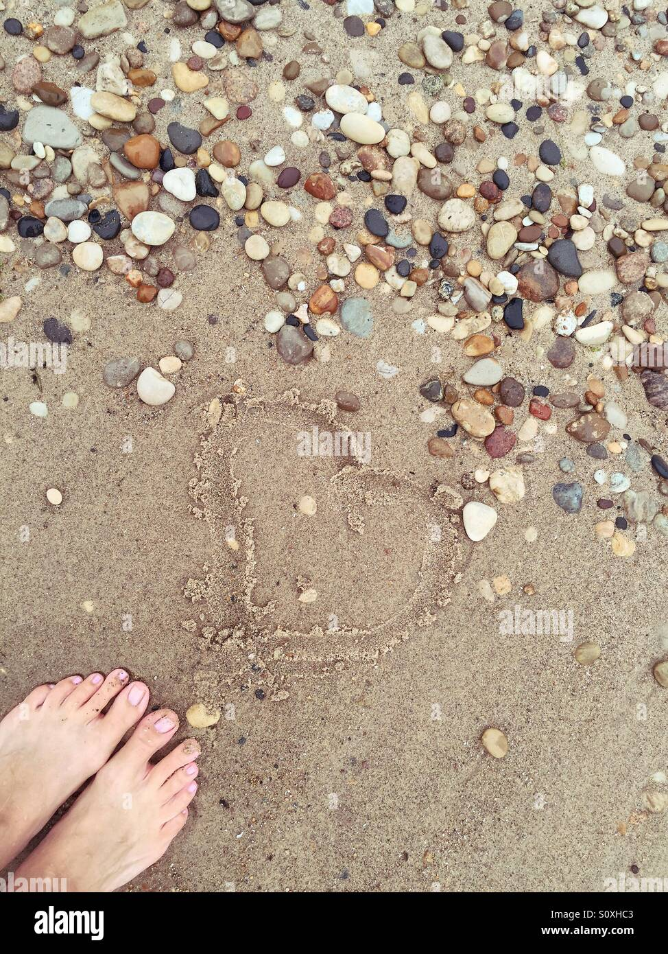 Heart traced into the wet sand on a beach, framed by beach pebbles and bare feet - Stock Image