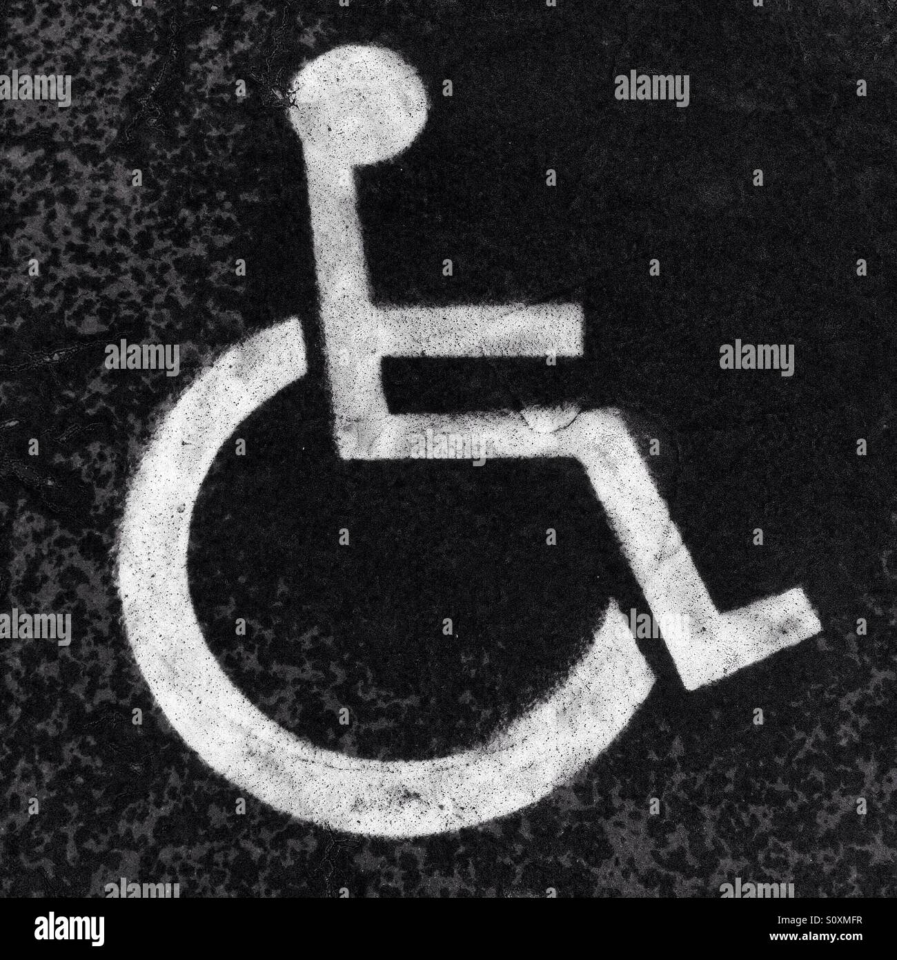 Handicapped sign painted on the road in black and white colors - Stock Image