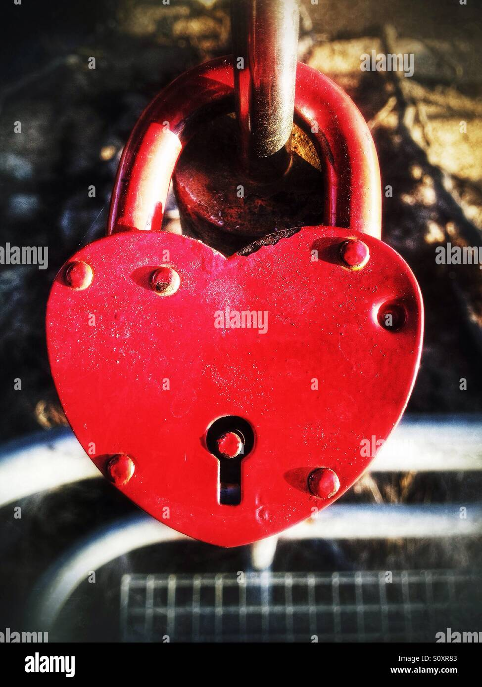 Lock with red heart shape on a bridge - Stock Image