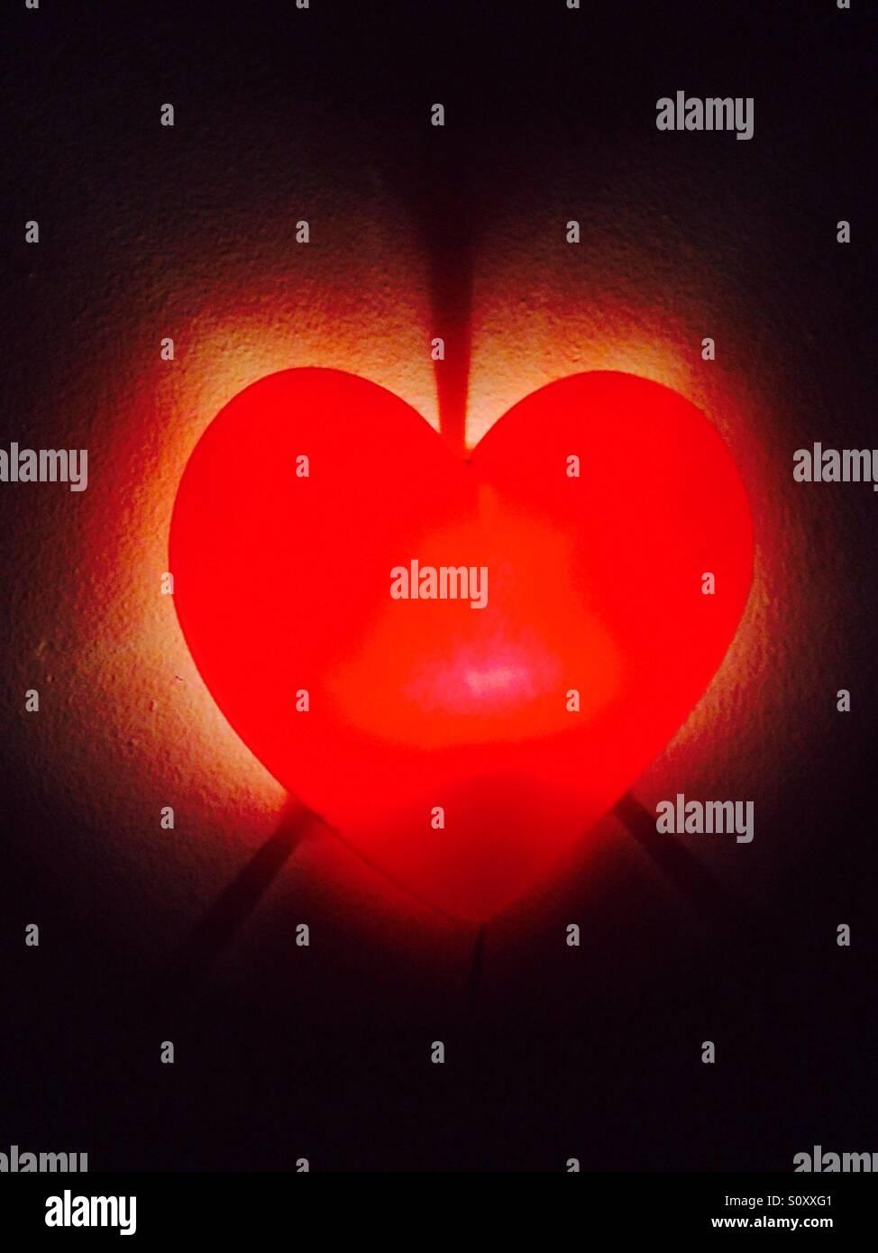 Red heart illuminated - Stock Image