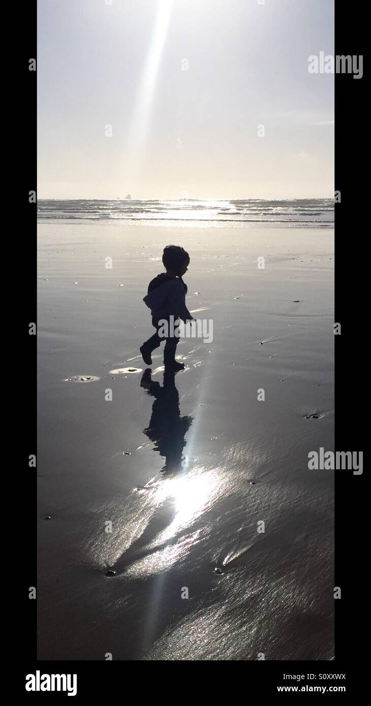 Silhouette of toddler on the beach - Stock Image