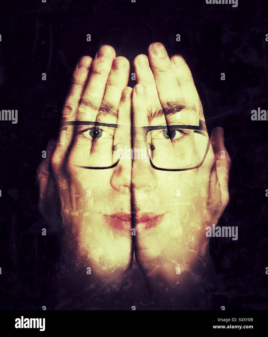 Handy Face an illusion of a persons face who is wearing glasses in their hands - Stock Image
