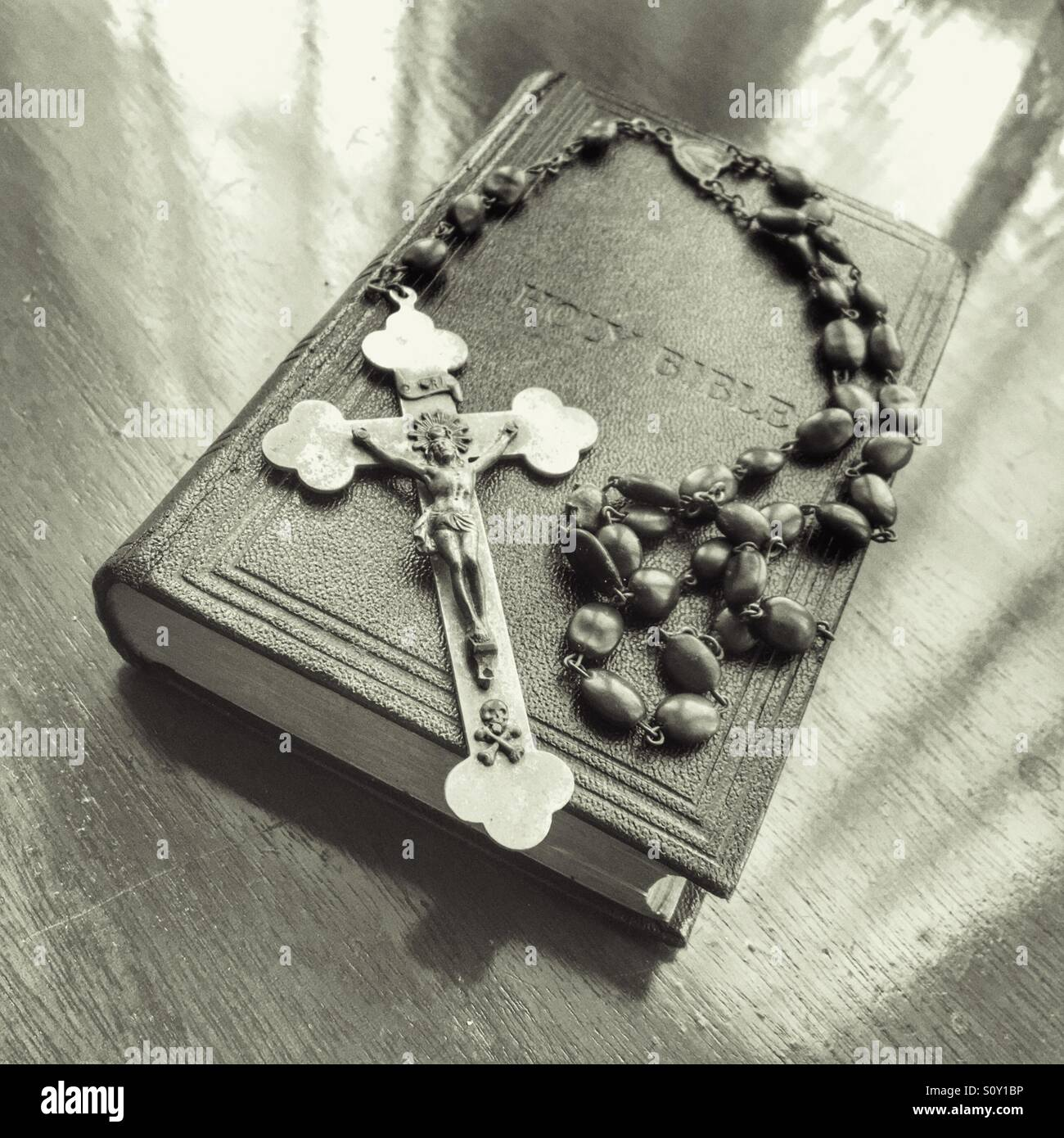 Rosary beads and crucifix resting on holy bible. - Stock Image
