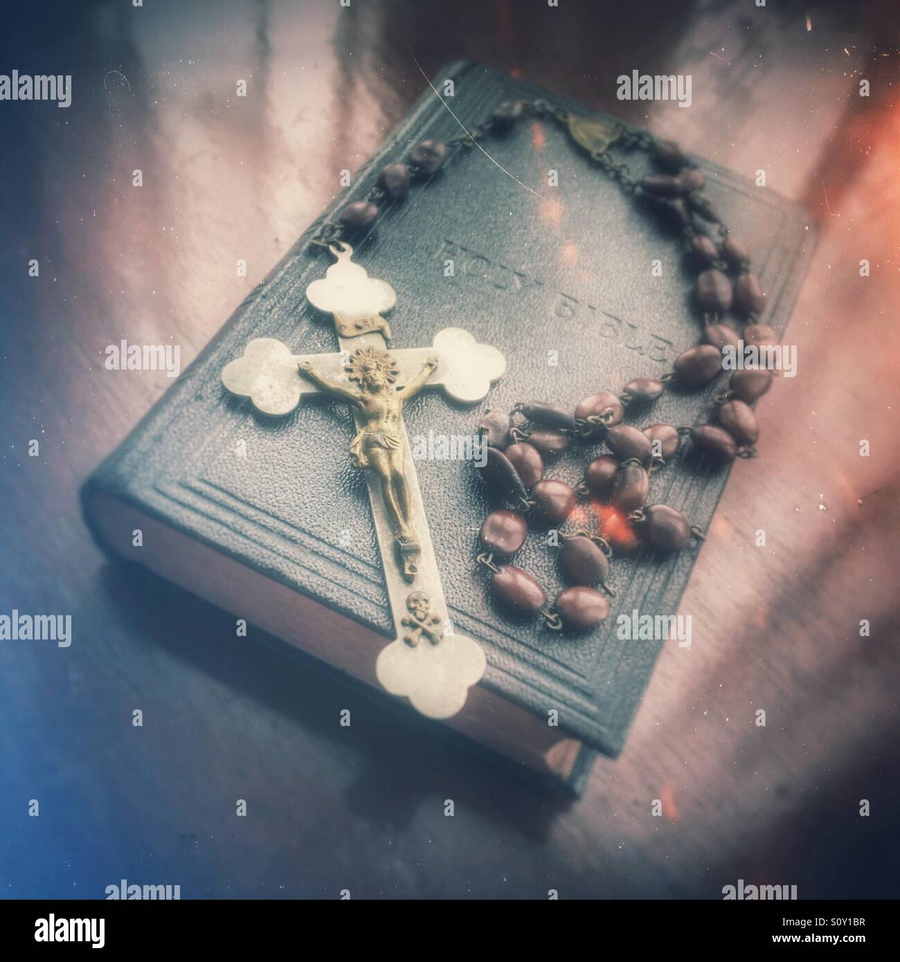 Rosary beads and bible resting on holy bible. - Stock Image