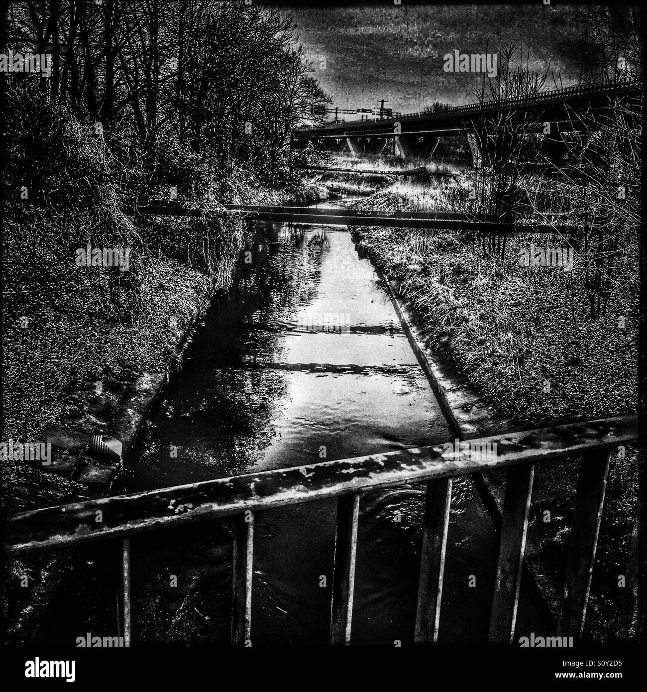 Apocalyptic view of river and viaduct in white and black - Stock Image
