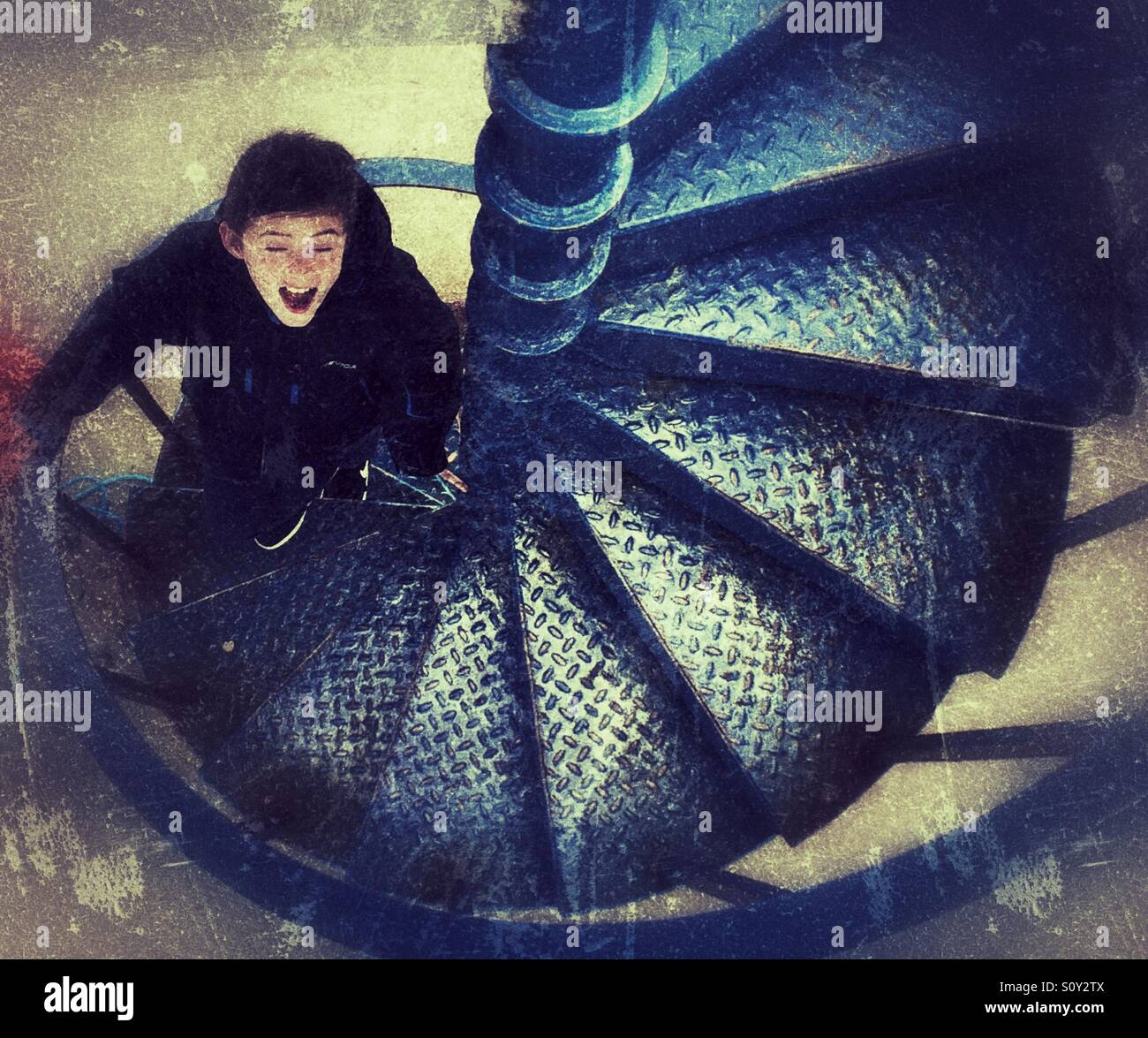 Eyes shut. Young boy walking up metal steps . - Stock Image