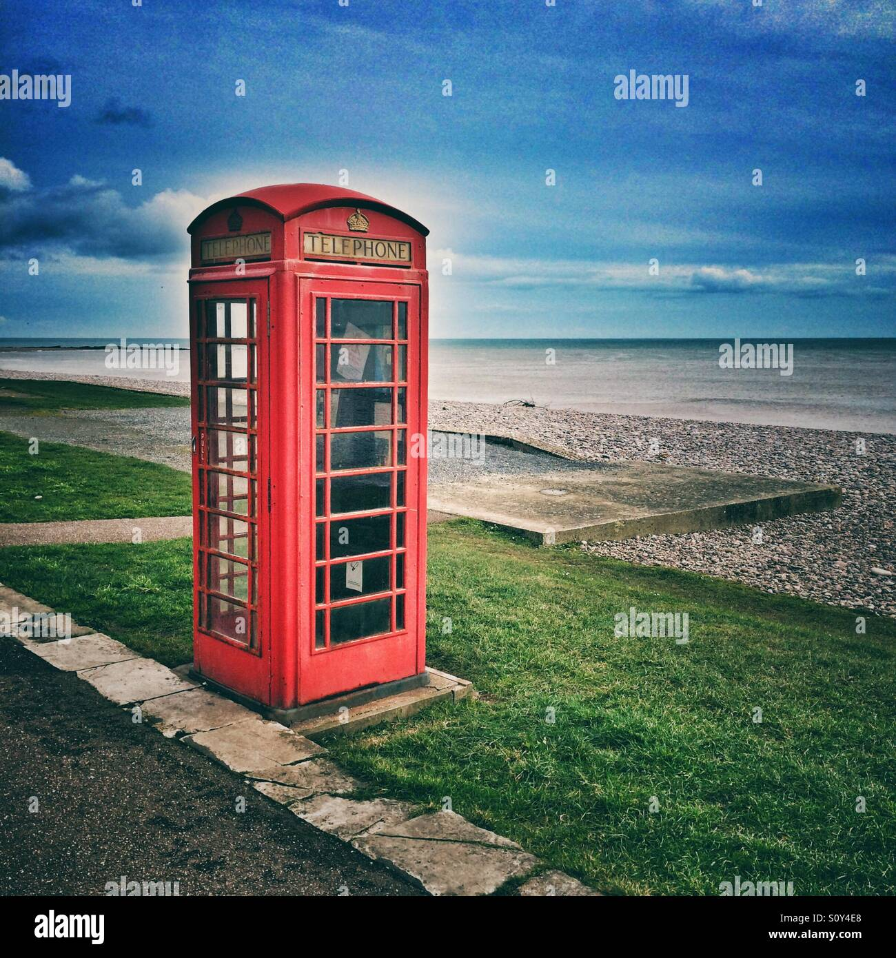 A red telephone box next to the sea - Stock Image