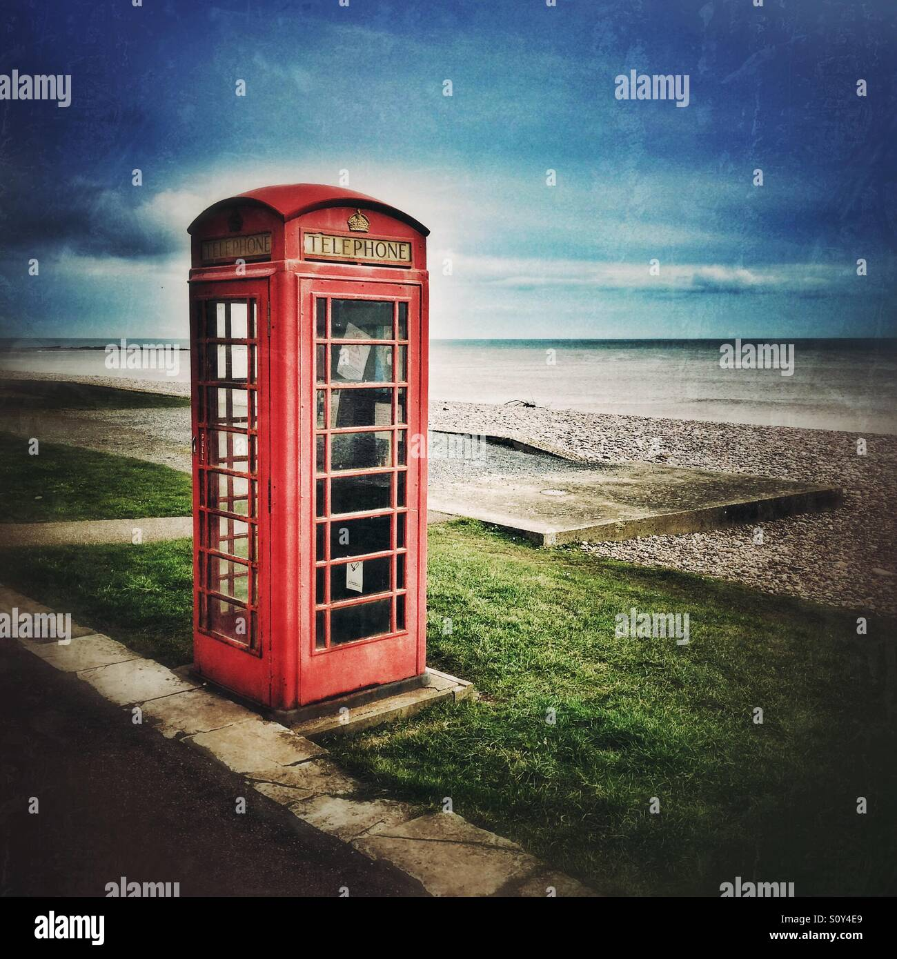 A red telephone box by the sea - Stock Image