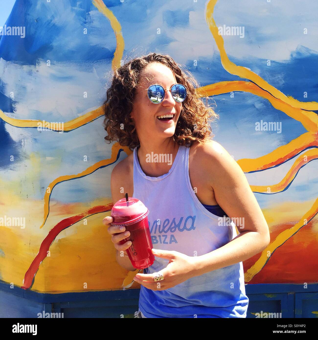 Woman smiling and holding healthy beverage - Stock Image