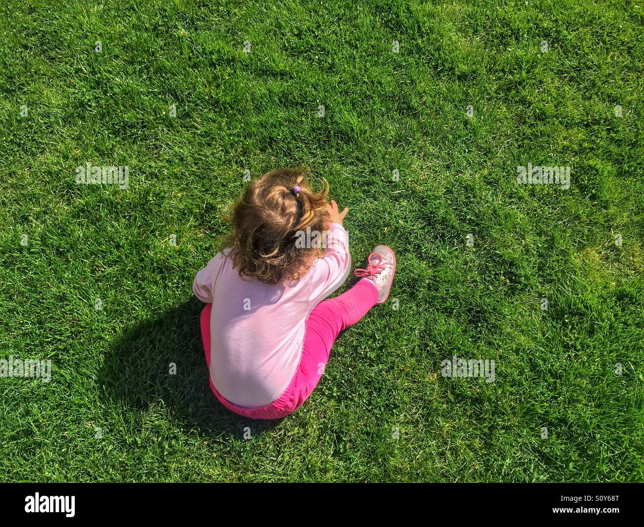 Baby girl sitting and expiring green grass - Stock Image
