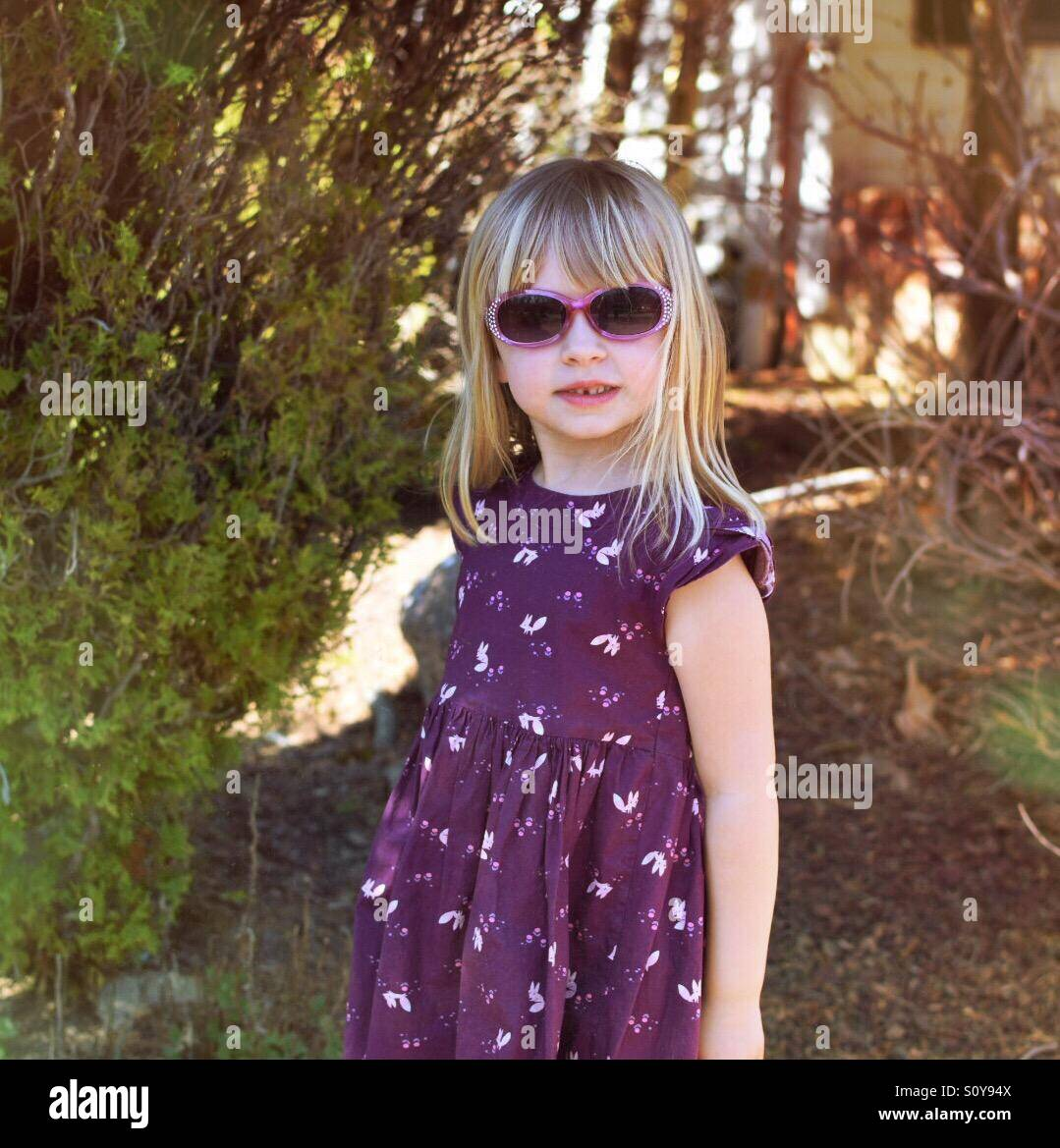 Young girl modeling sunglasses and purple dress outdoors - Stock Image