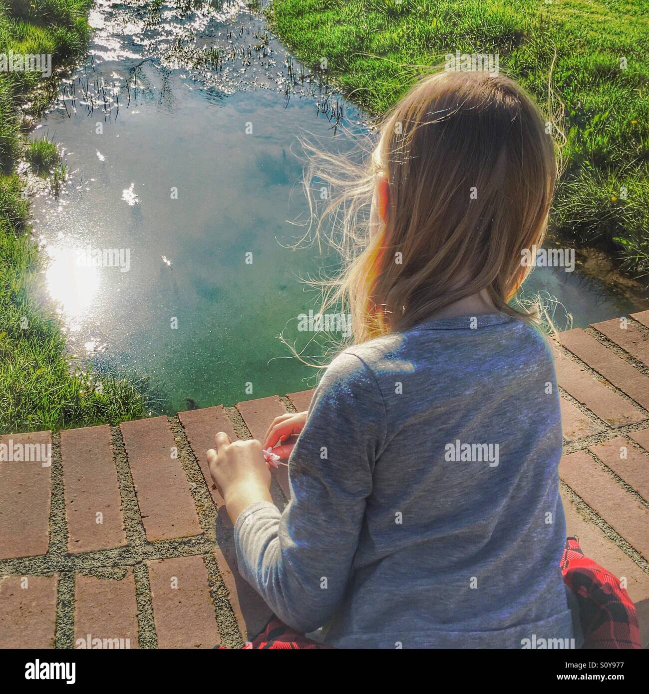 A girl dreaming by a stream. - Stock Image