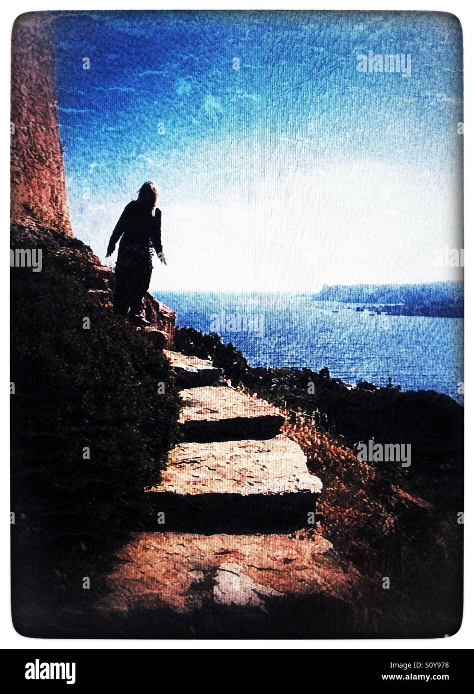 Woman on stone steps at oceans edge - Stock Image