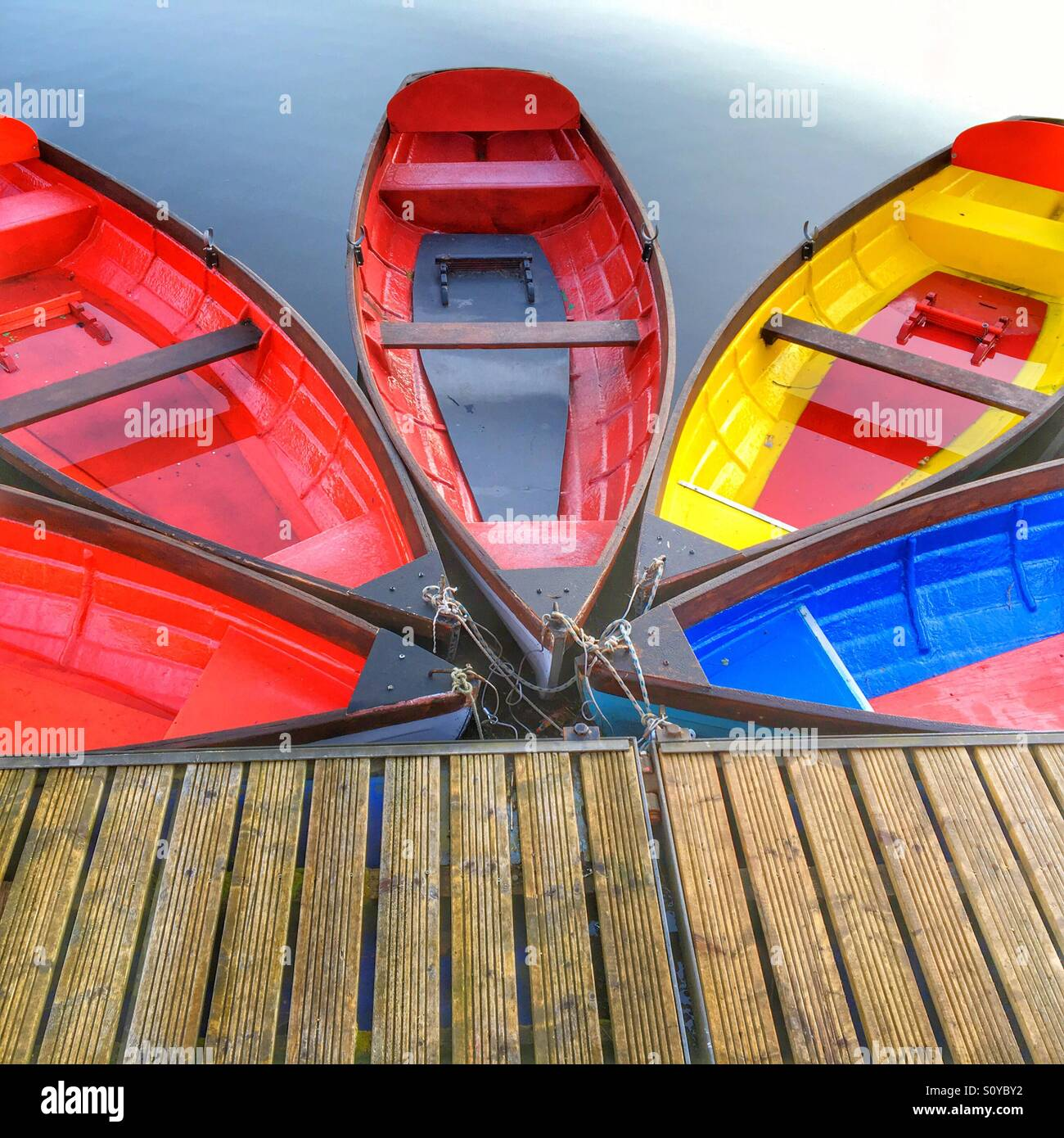 Five colourful rowing boats moored in a fan pattern - Stock Image