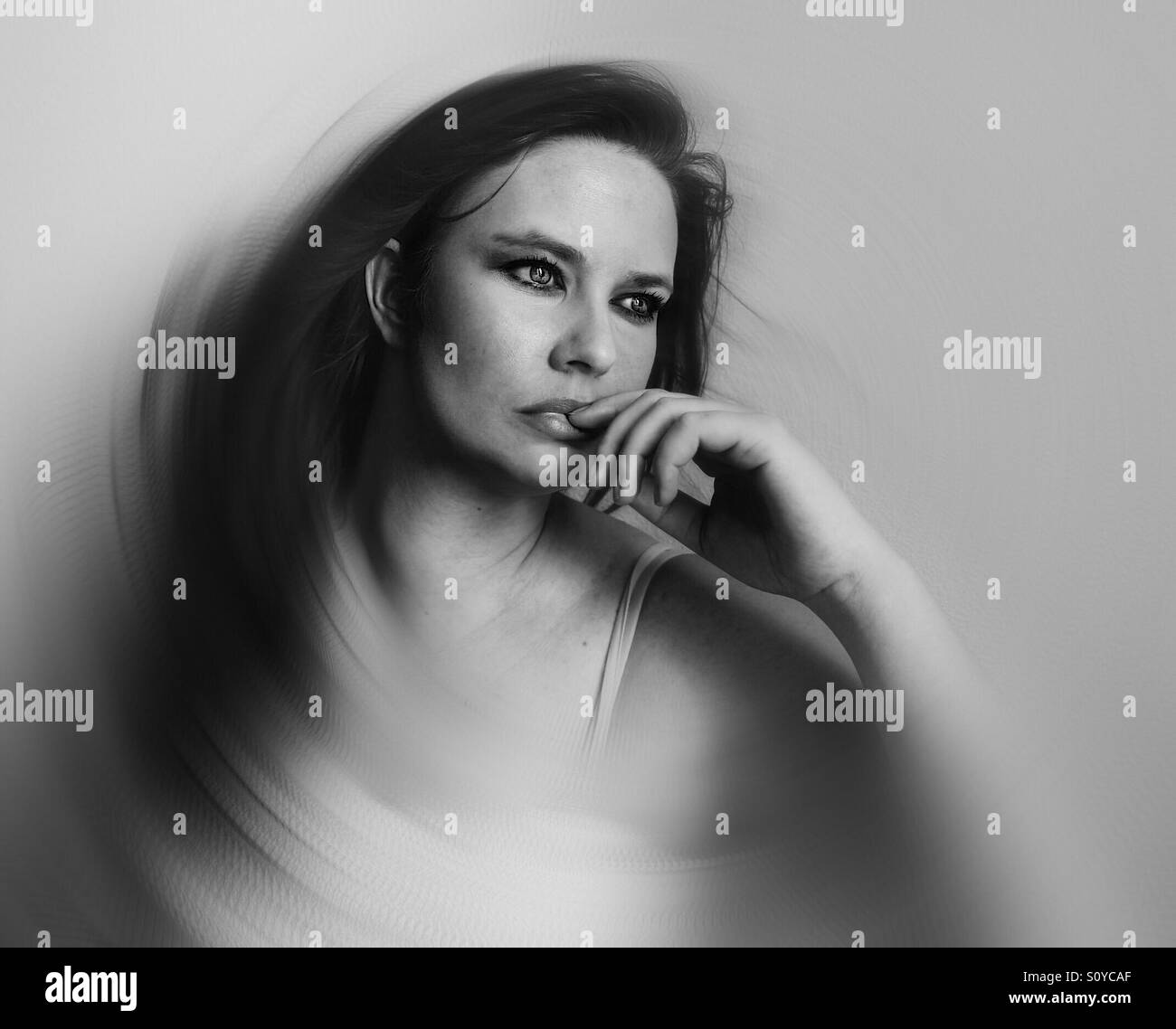 Creative blurred black and white portrait of woman in deep thought against wall - Stock Image