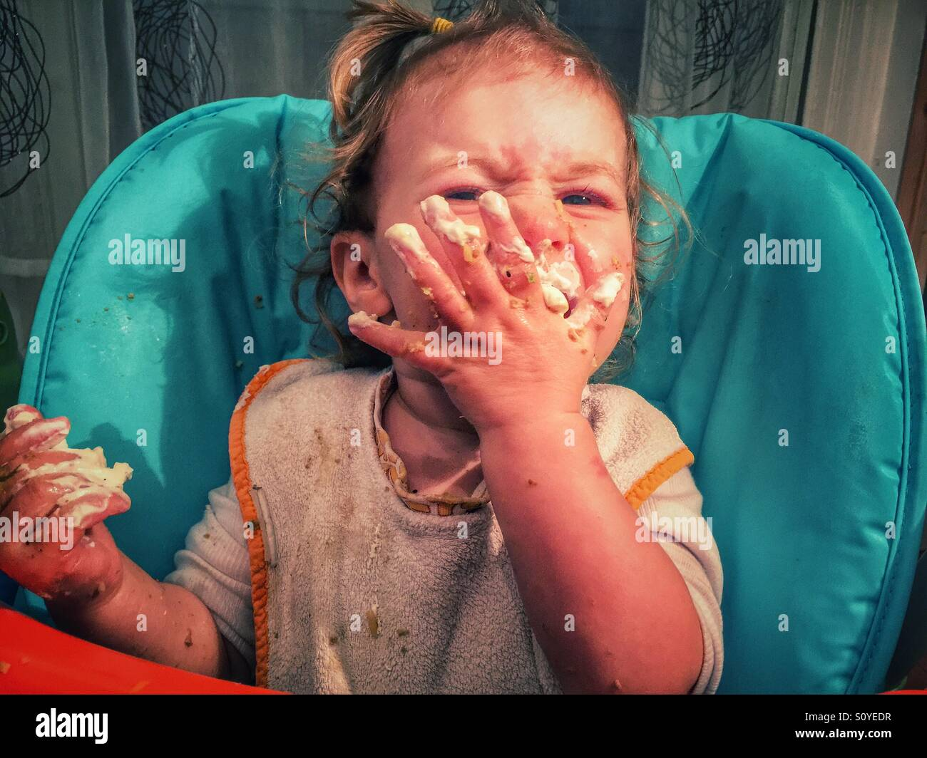 Baby eating messy face - Stock Image