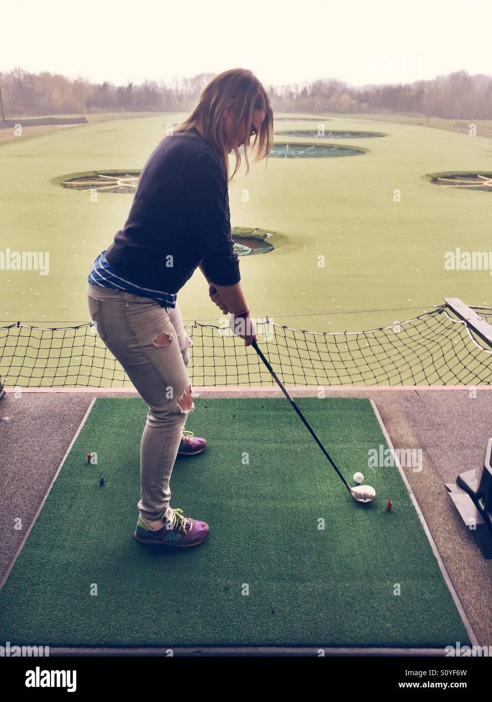 Girl playing golf at a driving  range - Stock Image