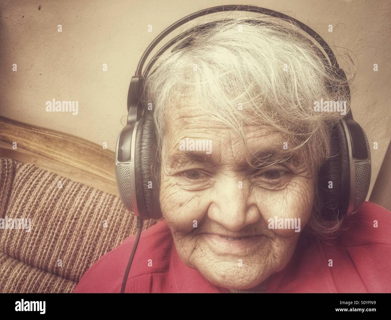 Elderly woman listen music - Stock Image