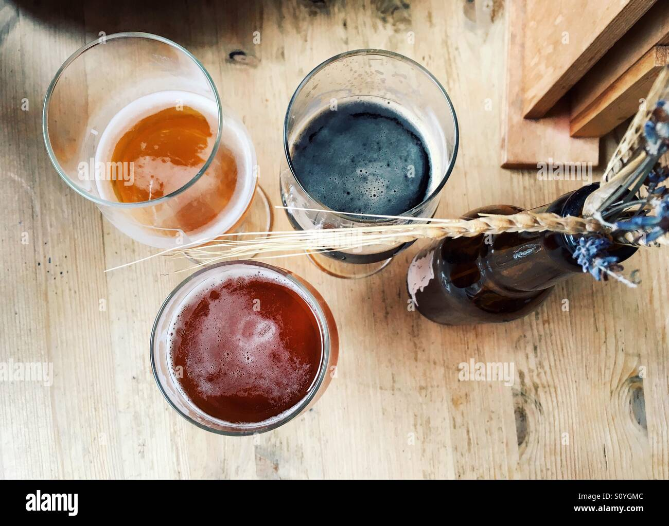 View from above of 3 different types of craft beer on a wooden table with decorative dried wheat and flowers on - Stock Image