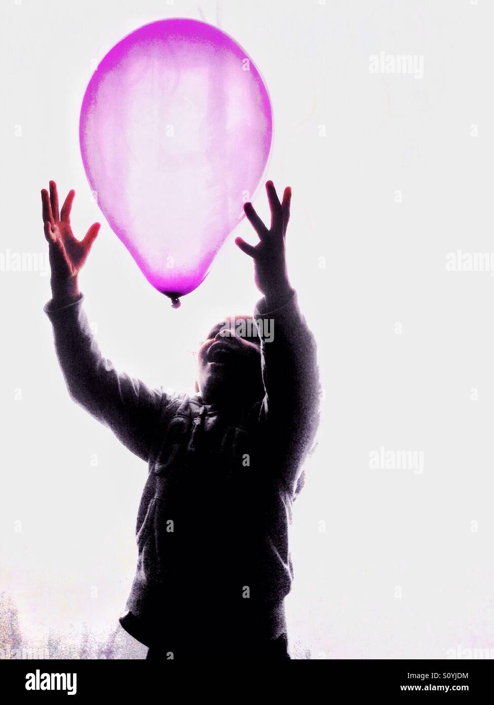 Boy catching a Pink balloon. - Stock Image