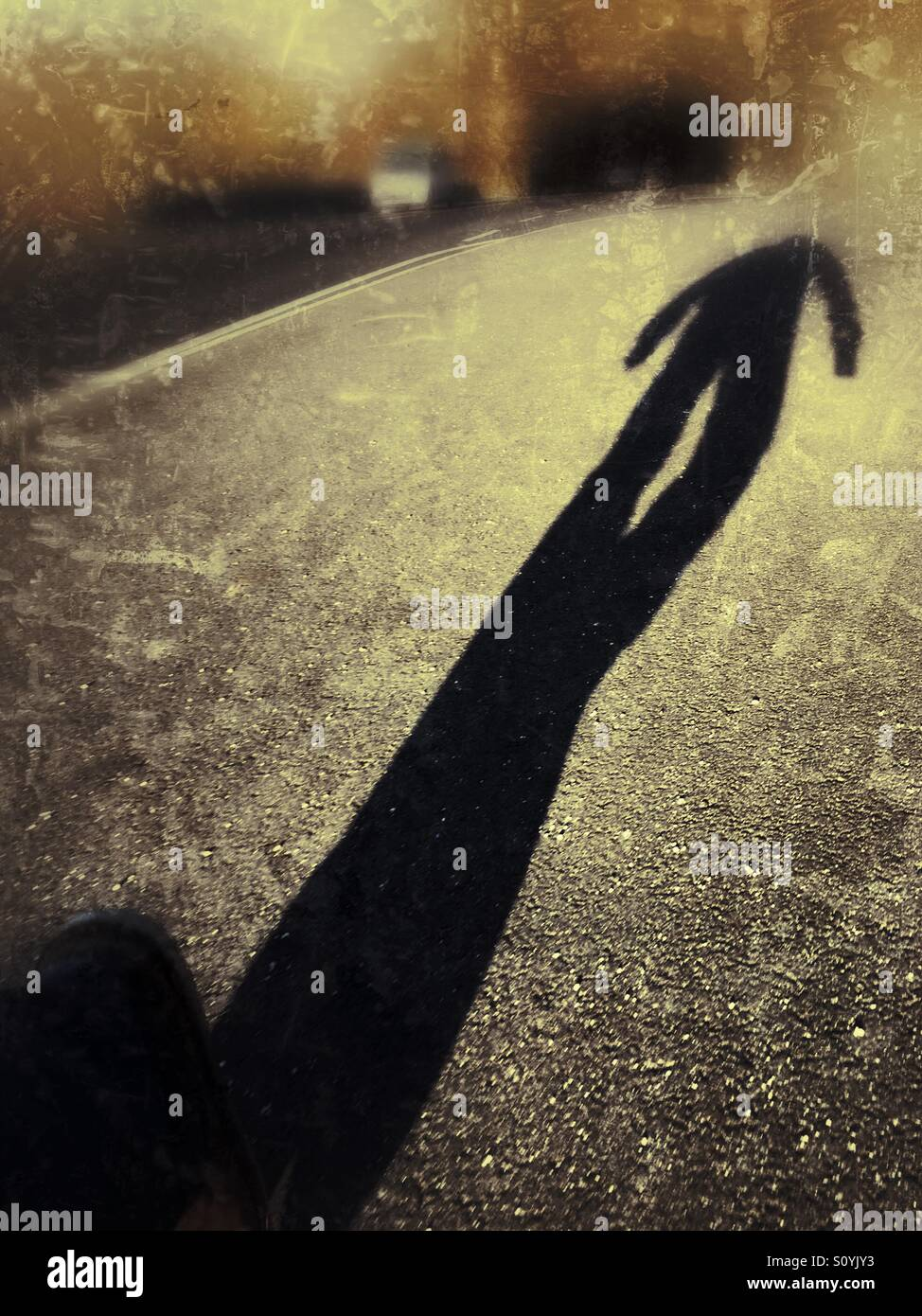 The long shadow of a man walking down a road. Stock Photo