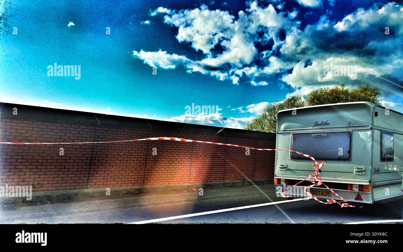 Caravan with red and white hazard tape hanging off on a motorway Stock Photo