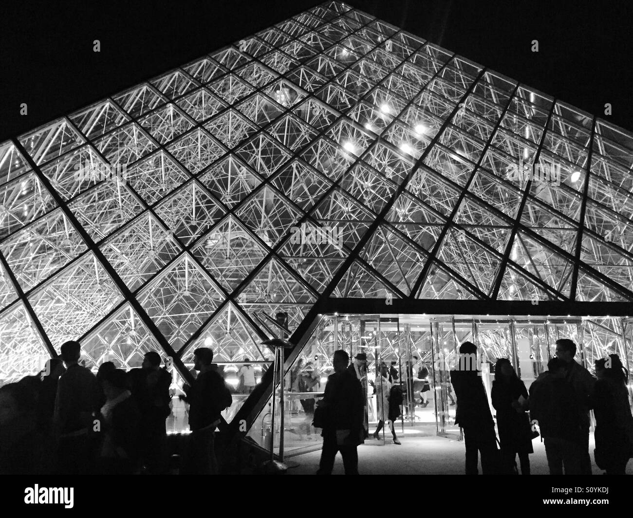 Silhouettes of people stand outside the class pyramid of the Louvre Museum in Paris. - Stock Image