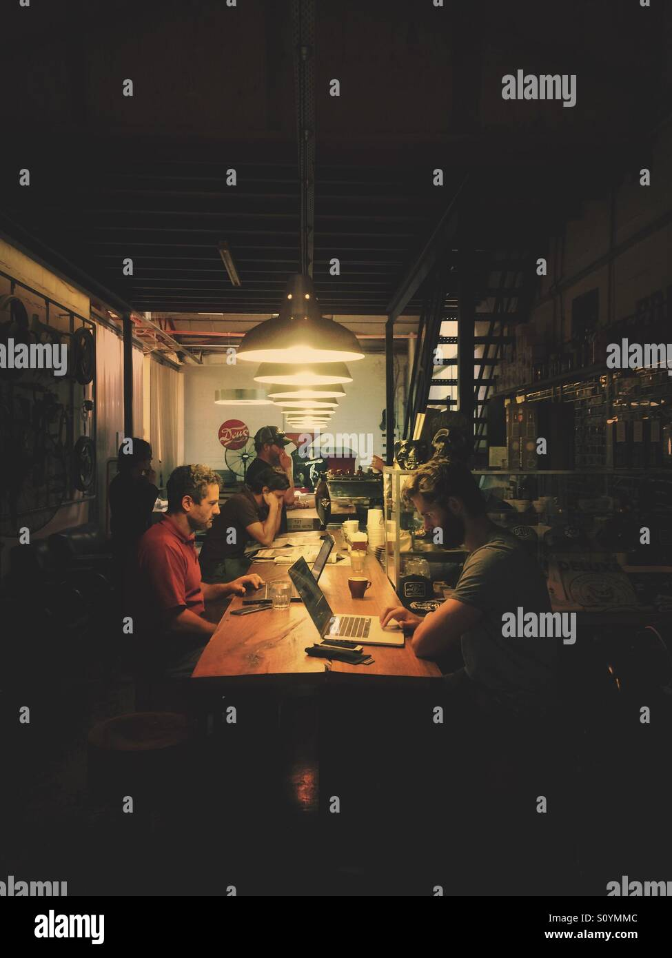 Freelancers working on laptops in coffeehouse. - Stock Image