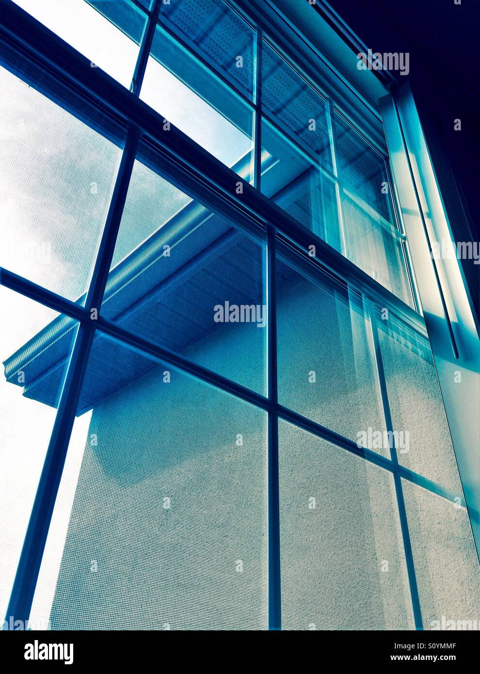 Window view with building detail in muted blue tones - Stock Image