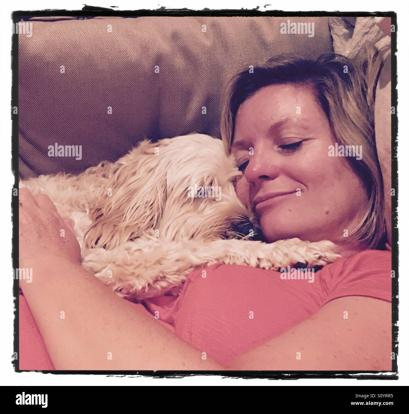 Dog asleep on woman female owner snooze time - Stock Image